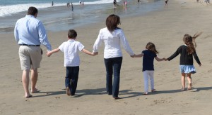 Happy family walking on beach after a successful family therapy session